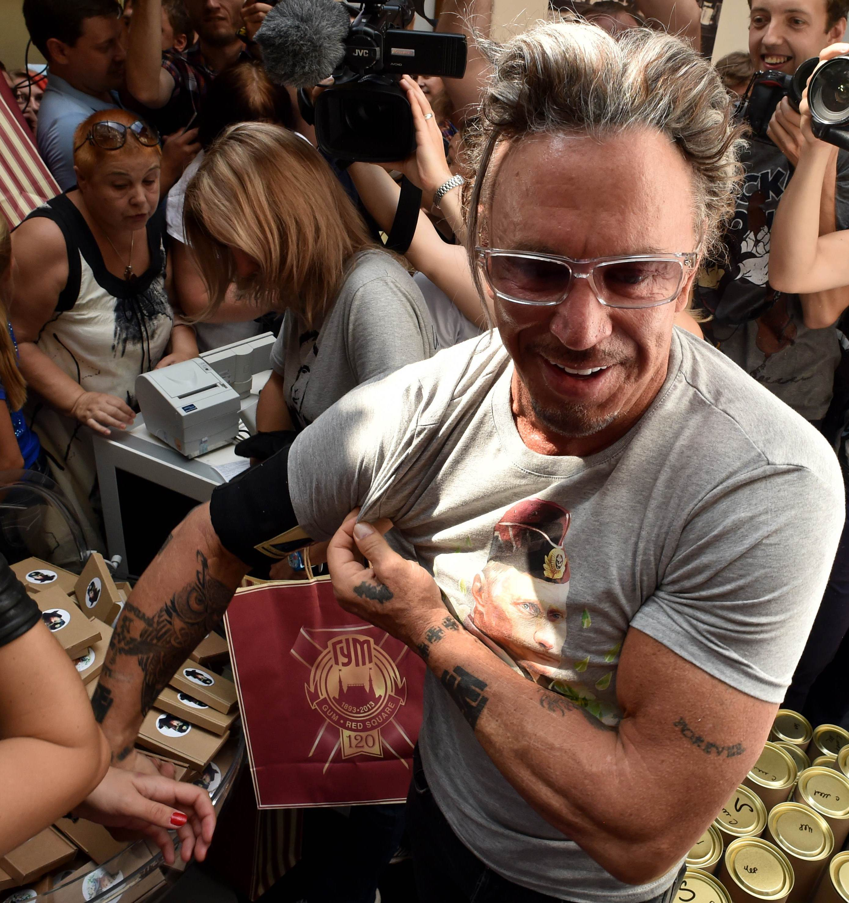 US actor Mickey Rourke (C) stands in front of journalists as he wears a T-shirt with the portrait of Russia's President Vladimir Putin in central Moscow on August 11, 2014. The sale of a new collection of T-shirts with Putin's portrait starts in the Russian capital on August 11, at a price of 1200 rubles (25 euros).  AFP PHOTO / KIRILL KUDRYAVTSEV