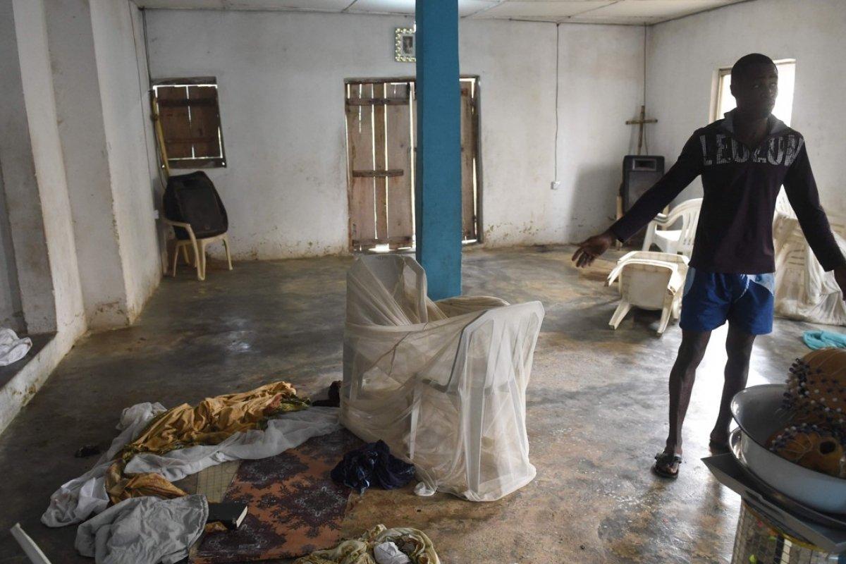 Мужчина указывает на пятна крови с места убийства четырех прихожан церкви в Оводо Онирин. Это тоже дело рук баду (фото: scmp.com)